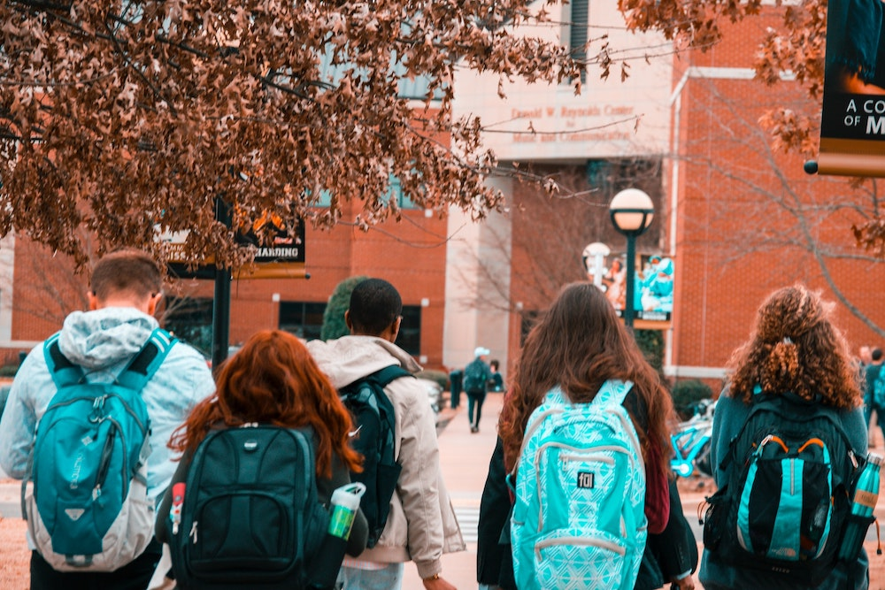 A group of students with backpacks going to school with the habits of successful students.